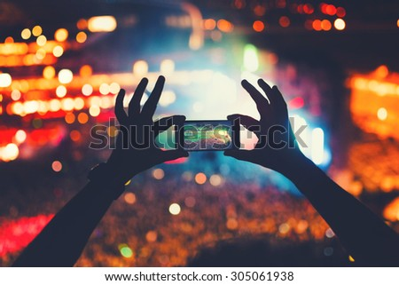 young hipster taking photos and videos at concert. Modern lifestyle with smartphone and parties. - stock photo
