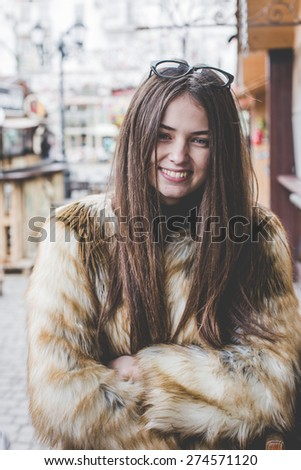 young hipster very beautiful caucasian stylish trendy girl with gorgeous brunette hair is having fun smiling outdoors on a background of the streets and wooden cool backgrounds during windy spring day - stock photo