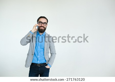 Young hipster with beard in glasses talking phone and smiling isolated on the blank white background - stock photo