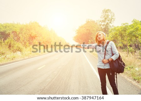 young hipster woman hitchhiking on countryside road - stock photo