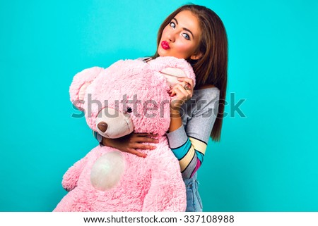 Young hipster woman playing with big fluffy pink toy bear, mint background, bright colors. Looking on camera hugs and sending kiss, candy colors sweater, bright make up, cute emotions. - stock photo