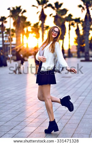 Young hipster woman posing on California beach at sunset, sunny autumn time, wearing trendy faux fur jacket and mini skirt, student with backpack, bright toned colors, jumping and having fun alone. - stock photo