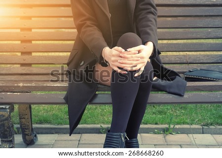 Young hipster Woman Sitting on Bench with her legs crossed part of the body image backlit - stock photo