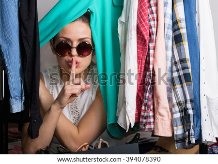 Young hipster woman sorting her wardrobe