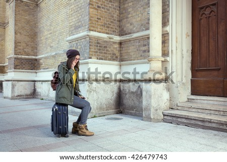 Young hipster woman taking on her mobile phone while sitting on a suitcase on the street of an old European town