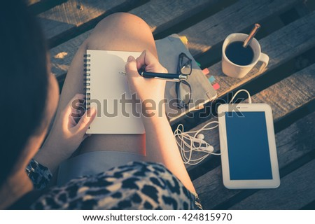 Young hipster woman writing journal on small notebook while sitting on wood bridge in morning time on weekend with high contrast sun lighting and vintage filter effect - stock photo