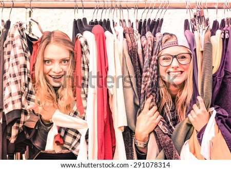 Young hipster women at clothes flea market - Best friends sharing fun time shopping in the city - Happy girlfriends enjoying happy life moments - Soft focus on warm vintage pink marsala filtered look - stock photo