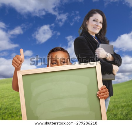 Young Hispanic Boys with Blank Chalk Board and Teacher Behind on Grass Field. - stock photo