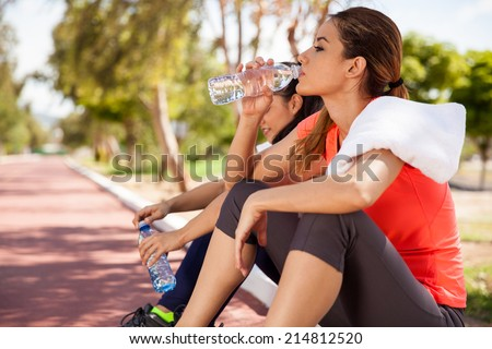 Young Hispanic brunette and her friend drinking water from a bottle after their workout - stock photo