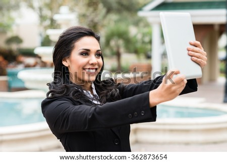 Young Hispanic businesswoman taking self-portrait selfie with digital tablet computer - stock photo