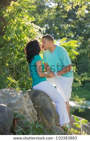 Young Hispanic Couple Engagement Picture Outdoor Portrait Back Lit by River Kissing Each Other