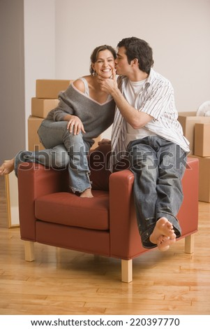 Young Hispanic couple kissing in new house - stock photo