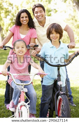 Young Hispanic Family Cycling In Park - stock photo