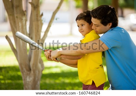 Young Hispanic father and his kid practicing a bat swing and spending time together at a park - stock photo