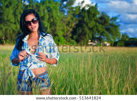 Young hispanic female beauty with sunglasses on green grass field