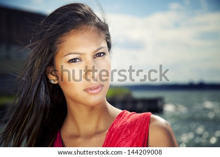 Young hispanic female by the water in red dress - stock photo