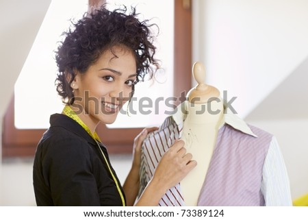Young hispanic female dressmaker adjusting clothes on tailoring mannequin and smiling at camera. Horizontal shape, side view, waist up