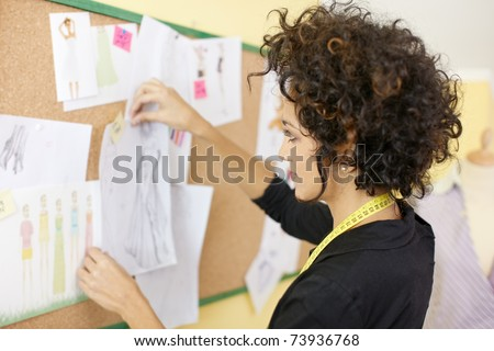 Young hispanic female dressmaker preparing show attaching drawings and sketches on board. Horizonta shape, side view, head and shoulders