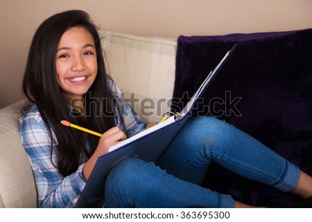Young hispanic girl doing homework on the couch - stock photo