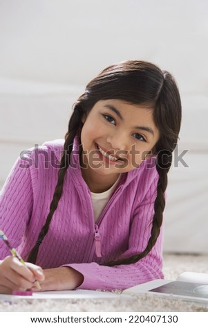 Young Hispanic girl doing homework on the floor - stock photo