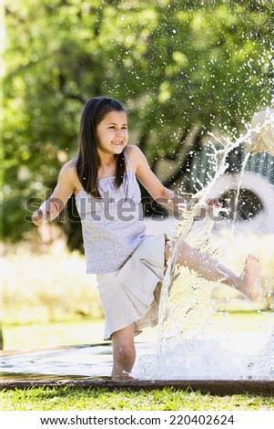 Young Hispanic girl playing in water outdoors - stock photo