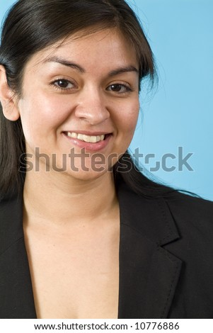 young Hispanic girl smiling for the camera in front of a blue screen - stock photo