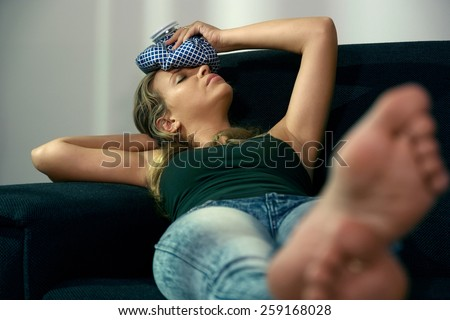 Young hispanic girl with headache feeling tired, laying on sofa at home, relaxing with feet on table and ice bag on head - stock photo