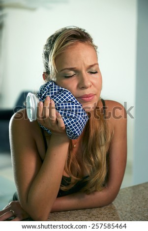 Young hispanic girl with tootache and dental problems, feeling pain and putting ice bag on mouth - stock photo