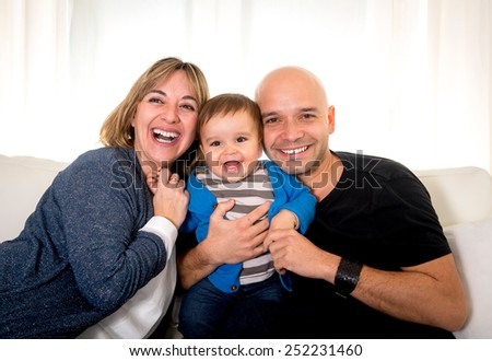 young hispanic happy mother and father holding little son sitting on couch together smiling and having fun playing with their small baby at home in parenthood concept - stock photo