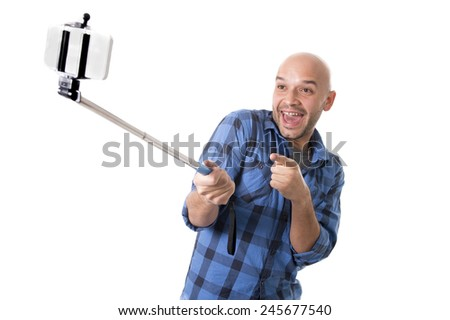 young Hispanic man in casual shirt having fun shooting mobile phone selfie picture or recording video holding stick playing with face expression isolated on white background - stock photo