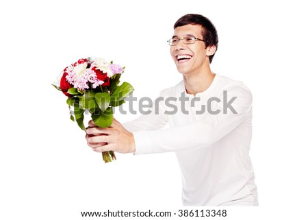 Young hispanic man in love wearing glasses and white long sleeve, giving bunch of flowers and happy smiling - dating concept