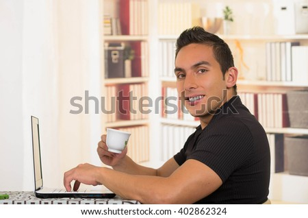 Young hispanic man sitting at desk holding small espresso cup and working on white laptop, profile angle - stock photo