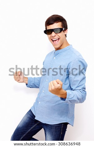 Young hispanic man wearing jeans and 3D TV LCD shutter glasses laughing and celebrating win with raised fists against white wall - 3D film concept - stock photo