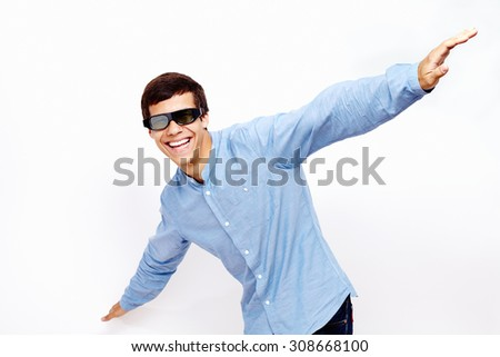 Young hispanic man wearing jeans shirt and 3D TV LCD shutter glasses laughing and having fun with hands outstretched lifted upwards against white wall - 3D film concept - stock photo