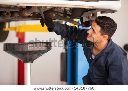 Young Hispanic mechanic draining engine oil from a car for an oil change at an auto shop - stock photo