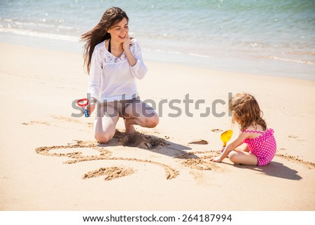 Young Hispanic mother and her little daughter drawing in the sand on a sunny day - stock photo