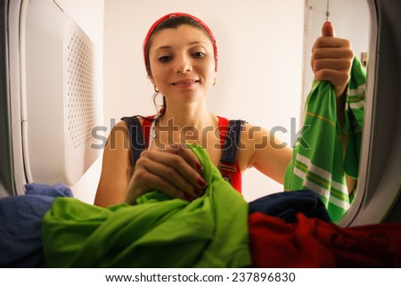 Young hispanic woman at home, doing chores and housekeeping, collecting clothes and dresses from laundry tumble dryer, drying machine - stock photo