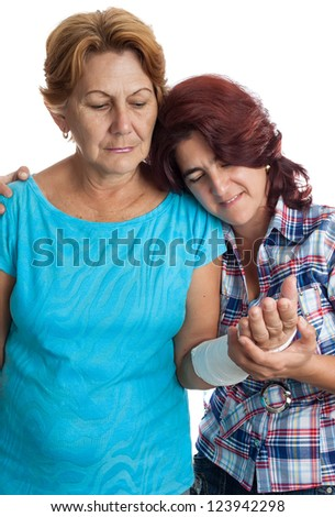 Young hispanic woman caring for an elderly lady with a broken arm (isolated on white)