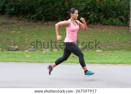 Young hispanic woman doing sprinting exercise in park