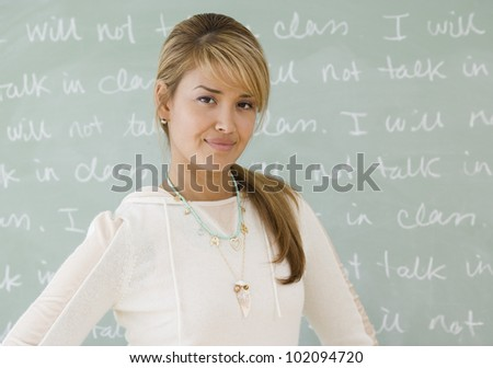 Young Hispanic woman in front of blackboard - stock photo