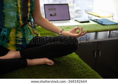 Young hispanic woman in office, sitting on desk covered with grass and plants. She meditates yoga in lotus position. Cropped view of hands and feet - stock photo