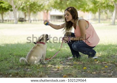 Young hispanic woman playing ball with her pug dog at the park - stock photo