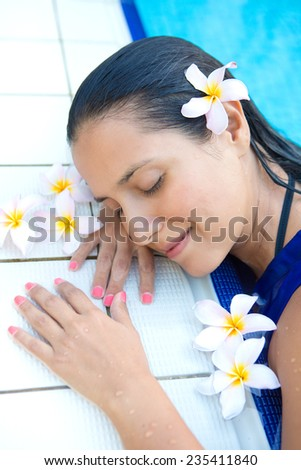Young hispanic woman with long black  hair, eyes closed relaxing by the swimming pool - stock photo