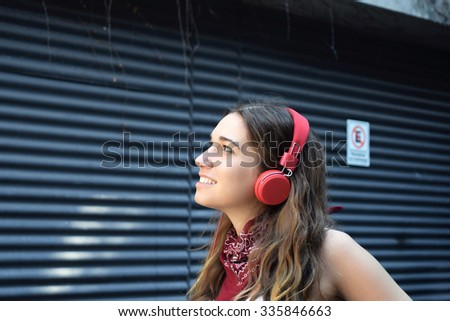 Young hispanic woman with red headphones. Trendy and urban style.