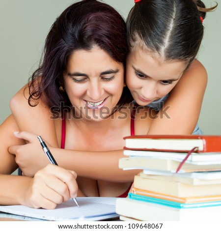 Young hispanic woman working or studying at home while her daughter hugs her from behind