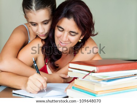 Young hispanic woman working or studying at home while her daughter hugs her from behind - stock photo