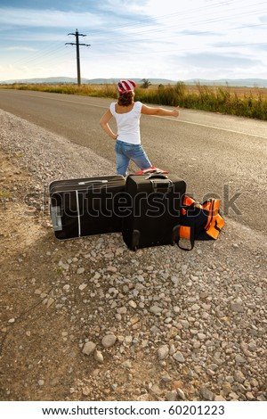 Young hitch-hiker girl standing on road side afternoon with suitcases