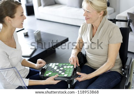 Young homecarer playing game with elderly woman - stock photo