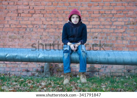 young homeless boy sits on a pipe with heating, city, street