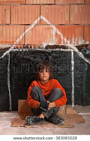 Young homeless boy sitting on the street - making an imaginary home - stock photo